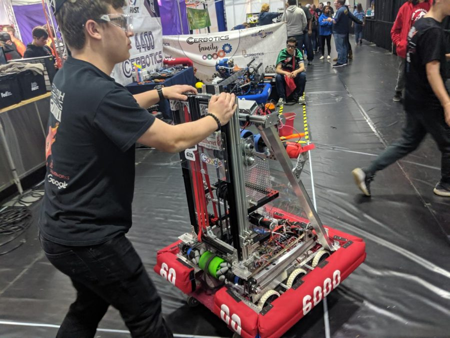 PREPARATION: In the gym at Da Vinci High School in El Segundo, junior Joey Blumofe pushed Shalhevet's robot toward the field to cue for the next match.