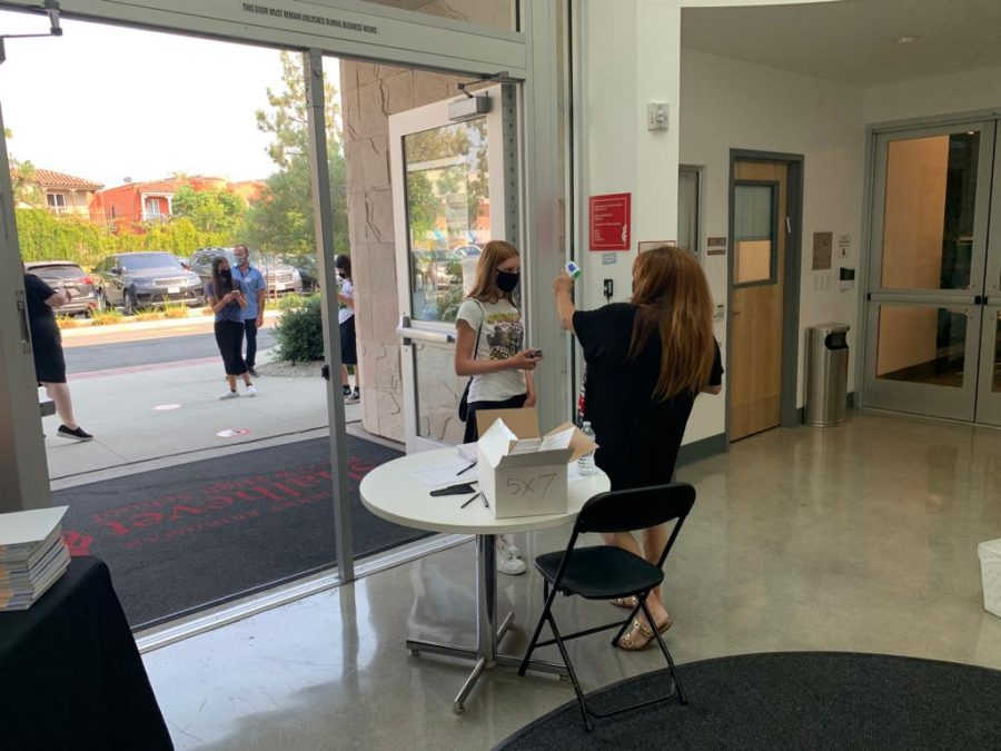 CHECK-IN: Mrs. Muriel Ohana, Assistant to the Head Of School, checked temperatures of students arriving for summer enrichment classes last month. Students arriving for Camp Firehawks and other activities should expect to have their temperature checked before entering the building.