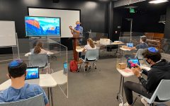 SAFETY: Dr. Josh Sharfman taught Computer Science in the Wildfire Theater during the first week of the summer classes. Desks were spaced six feet apart, and new plexiglass shields aimed to keep students' air to themselves.