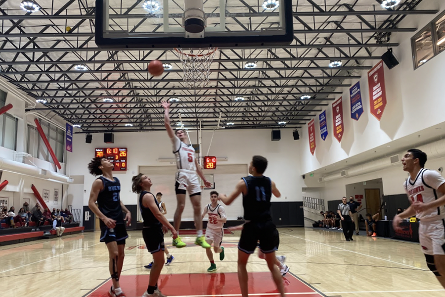 RESUMED: Firehawk shooting guard Jacob Pofsky launched a basket over the heads of defenders from Buena High School in Ventura Thursday night. Due to Covid rules, only 40 spectators, at left, were able to watch in person. Others watched a live but private video feed.