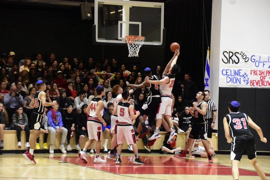 REBOUND: Firehawk forward Jacob Benezra '20 went for a rebound in November 2019 as the Frisch Cougars topped the Firehawks 56-51 in the championship game. A large crowd filled the Shalhevet gym, including a new seating area added that year for overflow.
