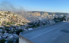 OVERLOOK: From the balcony of his dorm overlooking the Kotel, David Edwards '20 photographs smoke rising where fireworks had ignited grass fields after being launched from Silwan in East Jerusulam before Shabbat on May 14.